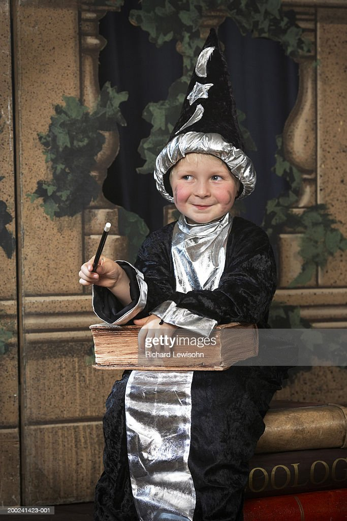 Boy (3-5) on stage in wizard costume, looking away, smiling : Stock Photo