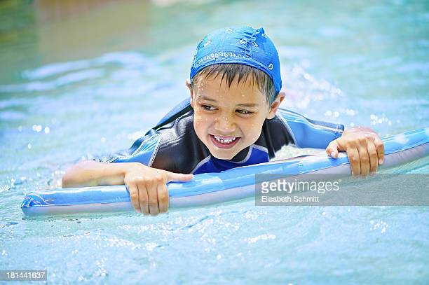 Boy on swimming board, laughing