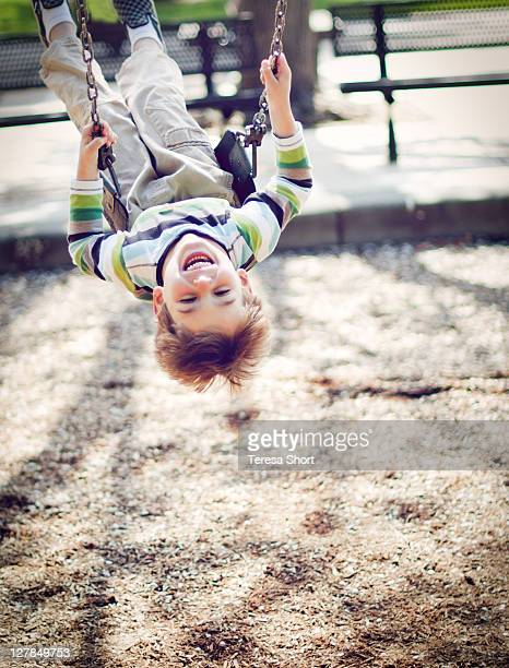 Boy on swing upside down