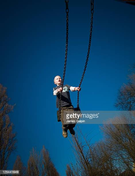 boy on swing with blue sky - streatham stock pictures, royalty-free photos & images