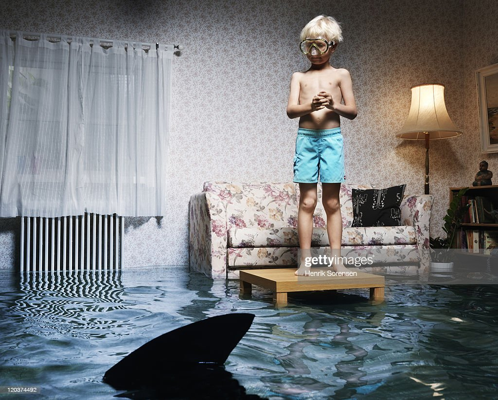 boy on table in flooded room, with shark : Stock Photo