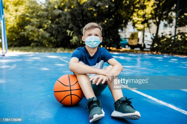 boy on the basketball field wearing a mask - coronavirus mask stock pictures, royalty-free photos & images