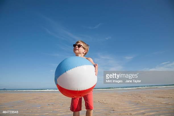 A boy on the beach holding a large inflatable beach ball.