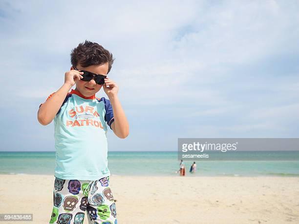 Boy on the beach wearing sunglasses