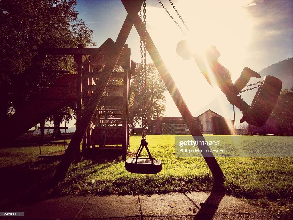 Boy On Tire Swing In Playground : Stock Photo