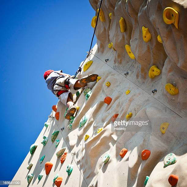 Boy on top of climbing wall