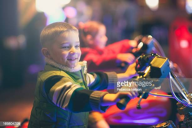 Boy on toy motorcycle at arcade