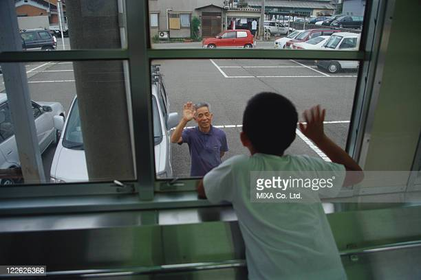 Boy on train waving goodbye to his grandfather
