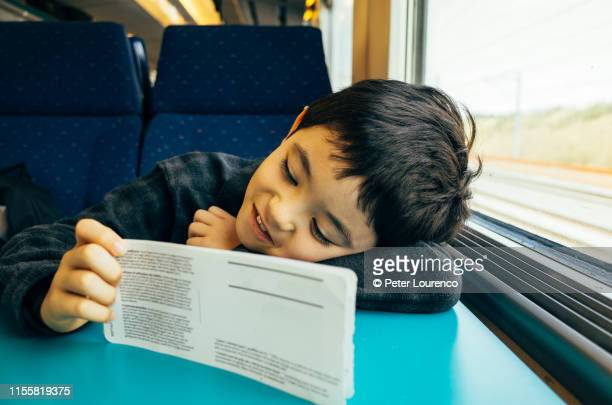 boy on train with train ticket - peter lourenco stock pictures, royalty-free photos & images