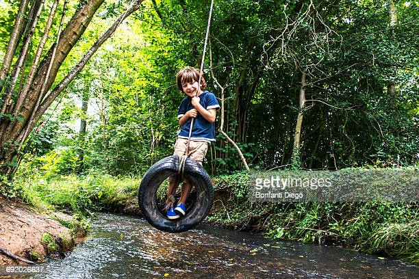 Boy on tyre using over river