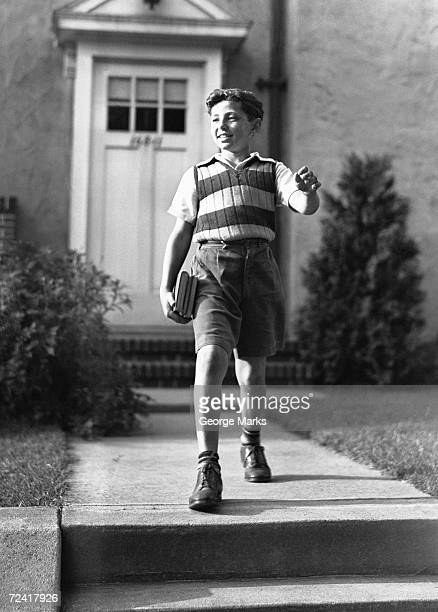 boy (10-11) on way to school, (b&w) - only boys stock pictures, royalty-free photos & images