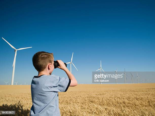 boy on wind farm looking through binoculars - only boys stock pictures, royalty-free photos & images