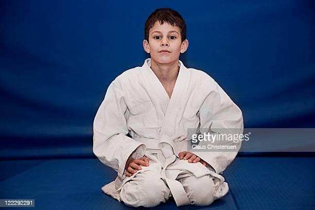 boy on yudo uniform on his knees at the doyo.