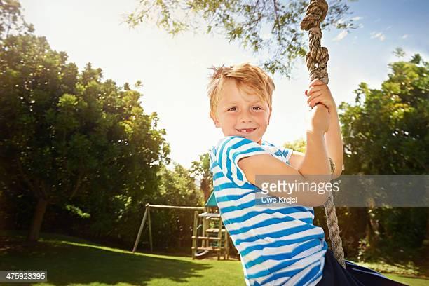 Boy on zip line swing, smiling
