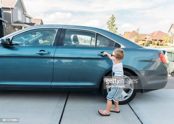 Boy opening blue car door in frontyard