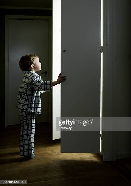 Boy (2-4) opening cupboard doors standing in light