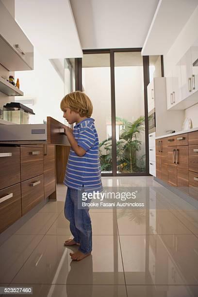 Boy (3-4) opening drawer