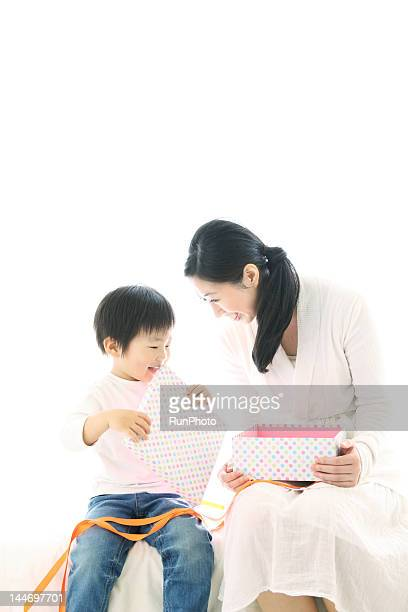boy opening gift box with mother
