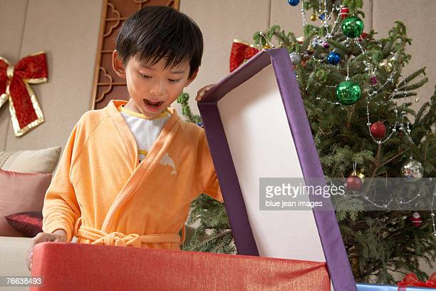 A boy opening his Christmas gifts.