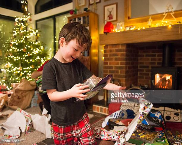 A boy opening his presents on Christmas Day throwing the wrapping paper to the floor.