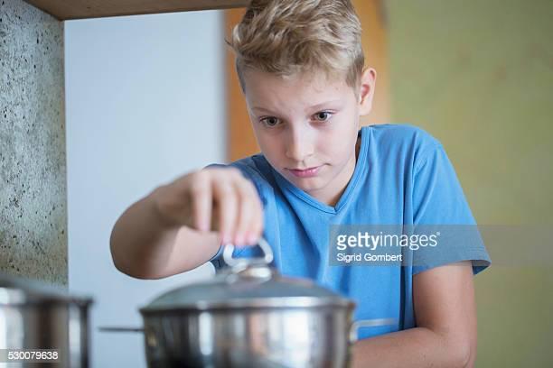 boy opening lid of cooking pan carefully, freiburg im breisgau, baden-w��rttemberg, germany - sigrid gombert stock pictures, royalty-free photos & images