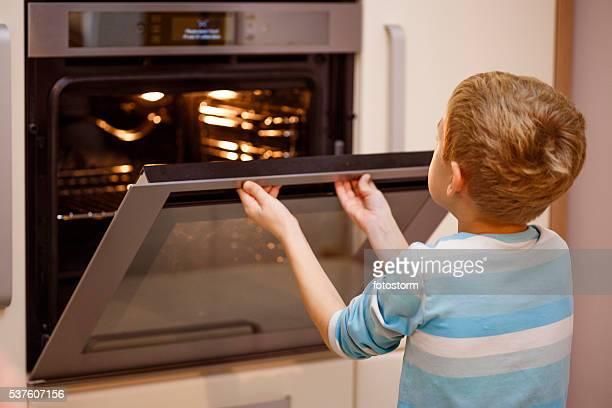 Boy opening oven, baking cookies