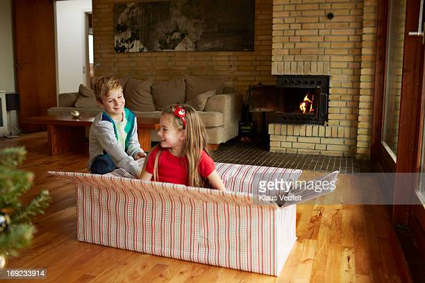 Boy opening present with his sister inside