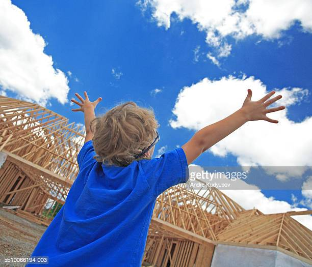 Boy (6-7) outstretching arms in front of new home construction, rear view