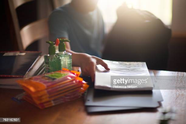 Boy packing backpack with school stationery supplies