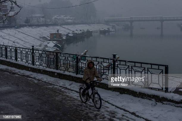 A boy paddles his cycle amid fresh snowfall on January 16 2019 in Srinagar the summer capital of Indian administered Kashmir India Kashmir Valley...
