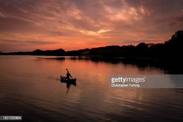 Boy paddles in his kayak at sunset on Pickmere Lake, Cheshire, on June 01, 2021 in Knutsford, United Kingdom. Warm weather across the UK has seen...