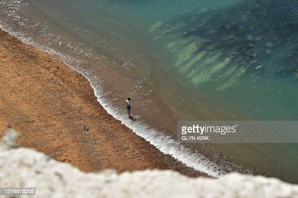 Boy paddles in the sea on Saltdean beach near Brighton on the south coast of England on June 2, 2020 following a further relaxation of the novel...