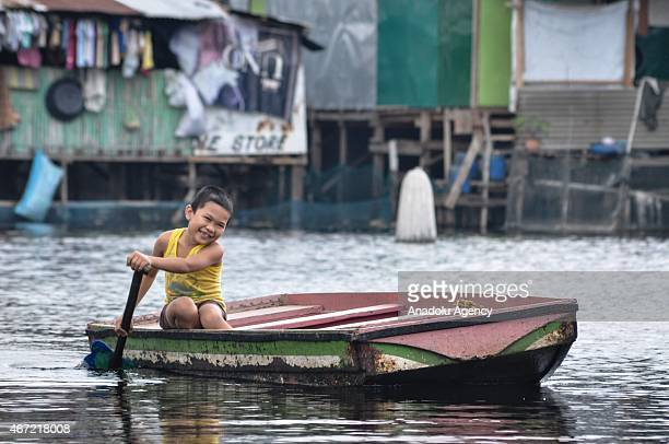 A boy paddles inside the submerged residential compund at Artex in Malabon City North of Manila on Sunday Today marks the celebration of the World...