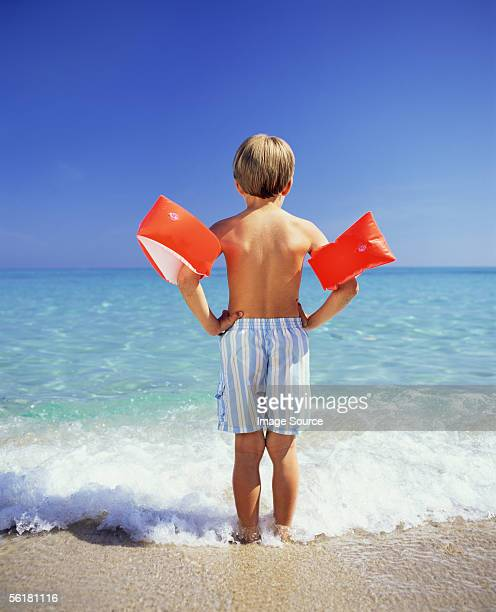 boy paddling with arm bands - armband stock pictures, royalty-free photos & images