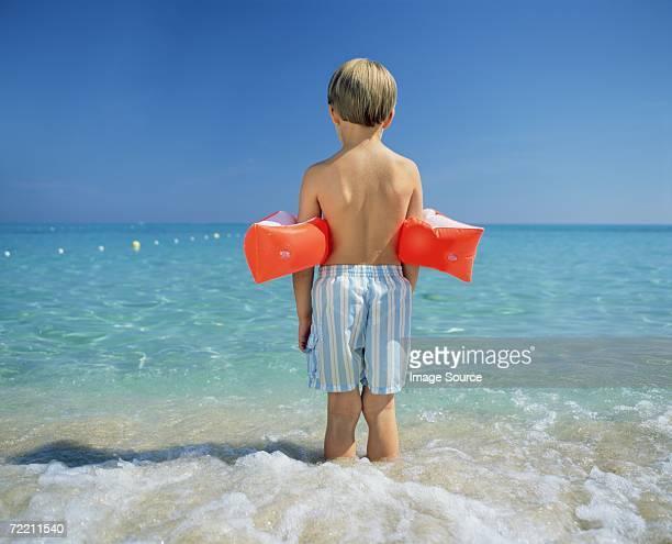 Boy paddling with armbands
