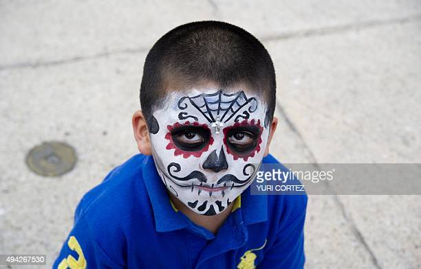A boy painted as Catrin poses for pictures at the Angel of Independence square before taking part in the Procession of the Catrinas along Reforma...