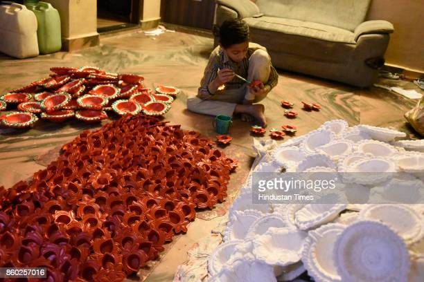 Boy painting earthen lamps for the upcoming Diwali festival at Uttam Nagar potters colony on October 3, 2017 in New Delhi, India.