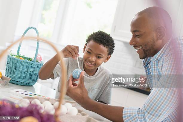 Boy (8-9) painting eggs in kitchen with his father
