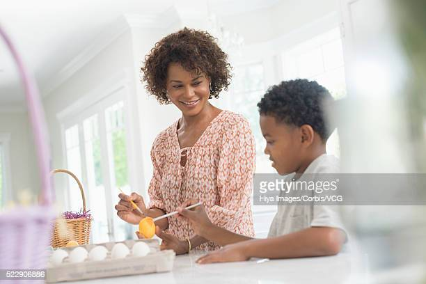 Boy (8-9) painting eggs in kitchen with his mother