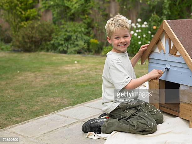boy (6-7 years) painting kennel in back yard, portrait - 6 7 years stock pictures, royalty-free photos & images