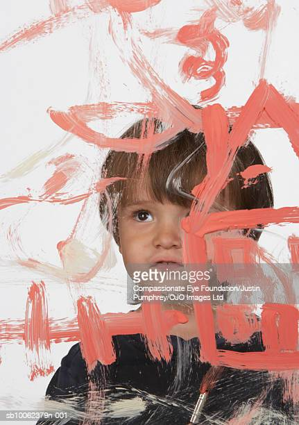 Boy (3-4 years) painting on glass, studio shot, portrait