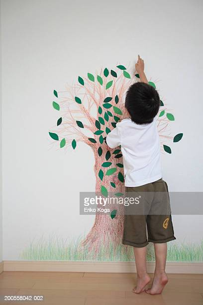Boy (4-5) painting on wall, rear view
