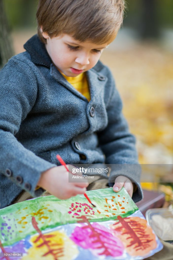 Boy paints a picture in the autumn forest. : Stock Photo