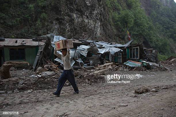 A boy pass through a collapsed abandoned village as he's carrying goods found in a destroyed Chinese truck at 30 minutes walk from here on the...