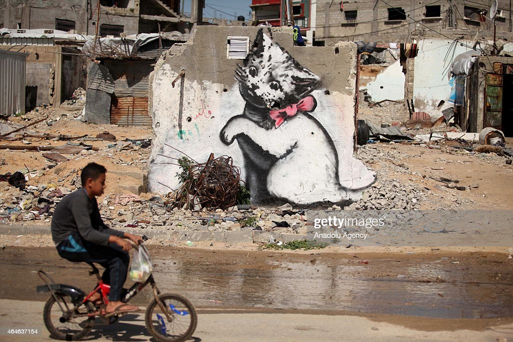 A boy passes by a graffiti on a wall of a building drawn by British artist Banksy in Beit Hanoun, Gaza on February 27, 2015. Famous British artist Banksy visited Gaza and drew graffiti on the walls of houses in Beit Hanoun destroyed in Israel's recent attacks on Gaza.