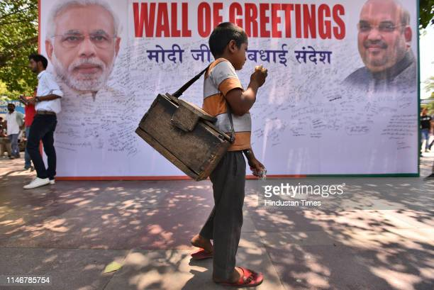 A boy passes by a temporary Wall of Greetings organised by BJP at Rajiv Chowk on May 28 2019 in New Delhi India