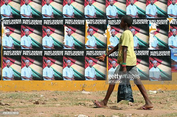 A boy passes by electoral posters of independent candidate to the presidential elections in the Republic of GuineaBissau Nuno Gomes Nabiam in a...