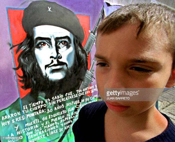 A boy passes in front of a painting of Ernesto Ché Guevara 24 October 2000 in a street of Caracas Venezuela Traveling merchant offers these paintings...