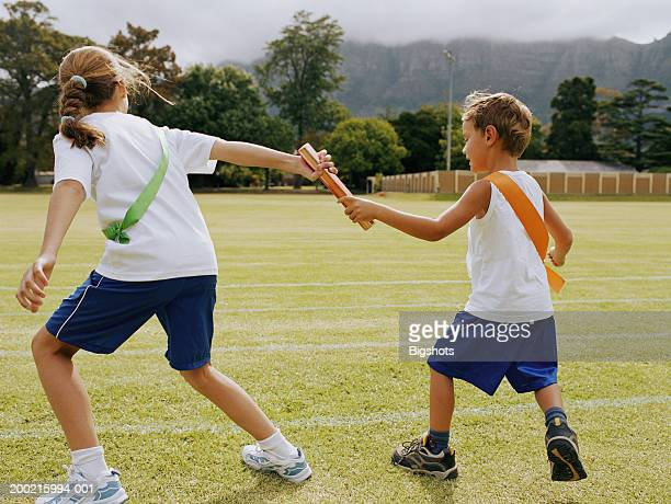 boy (3-5) passing relay baton to girl (7-9) on running track - passing sport stockfoto's en -beelden