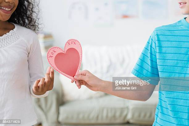 boy passing valentine to friend - valentines african american stock pictures, royalty-free photos & images